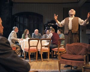 The Berger family (seated l-r, Victor Talmadge, Rebecca White, Charles Dean, Anthony Nemirovsky, Patrick Russell, Ellen Ratner) has dinner while Jacob (r, Ray Reinhardt) talks to Moe (l, Rod Gnapp) in Awake and Sing! Photo by David Allen
