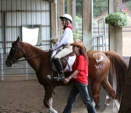 SonRise Equestrian Foundation participant Roxanne Fernandes and volunteer  Kathy Barlow enter the Charles Wilhelm Training Center with horse Molly,  painted with the logo of Murrieta's Well Winery, the event's Presenting Sponsor