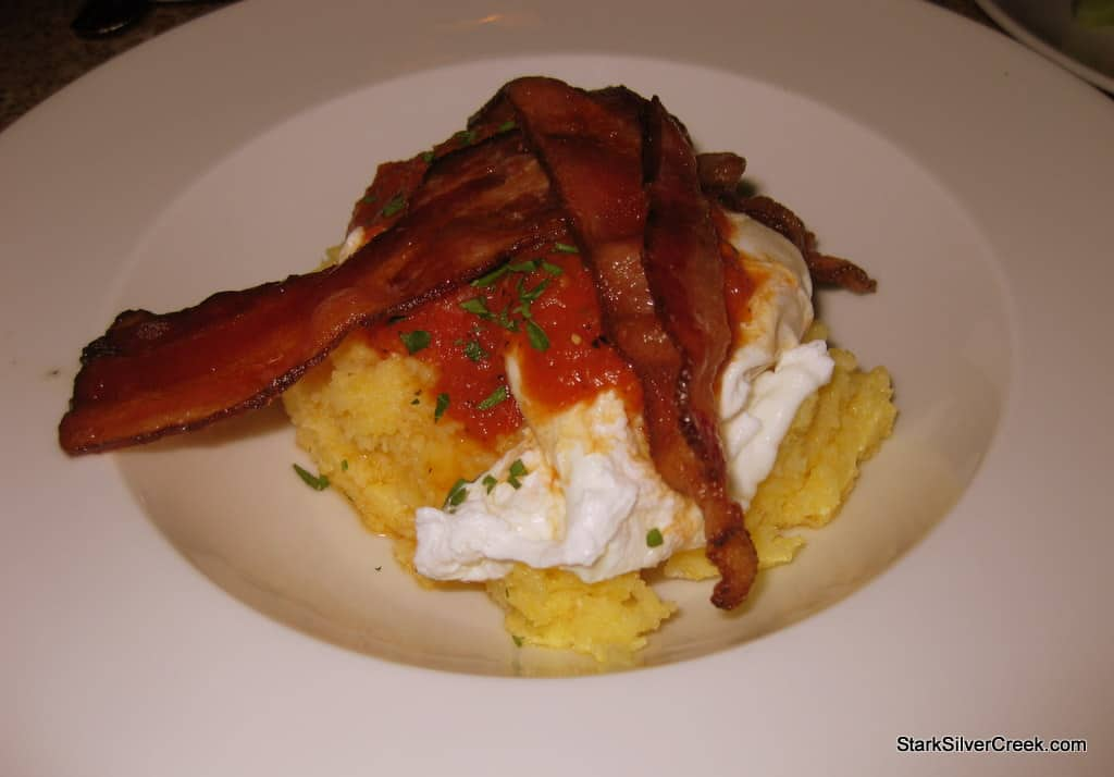 Breakfast of polenta, poached eggs and bacon.