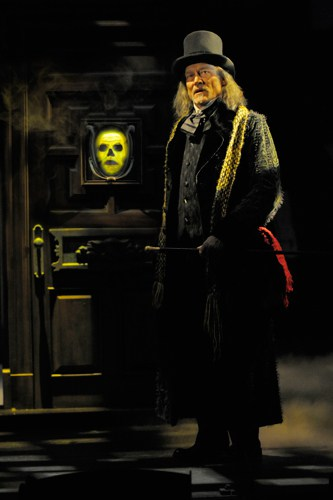 Ebenezer Scrooge (James Carpenter) finds an unexpected apparition on his door.