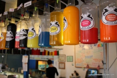 Single file line of colorful bottles of flavor. For some Shave Ice purists, they prefer seeing these bottles chilled so that when the liquids hit the Shave Ice ball, it is less likely to melt the little pieces of ice together.