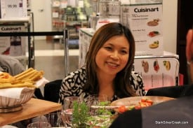 Loni enjoys dinner conversation, in front of small appliances while Martha Stewart and Emeril look down.