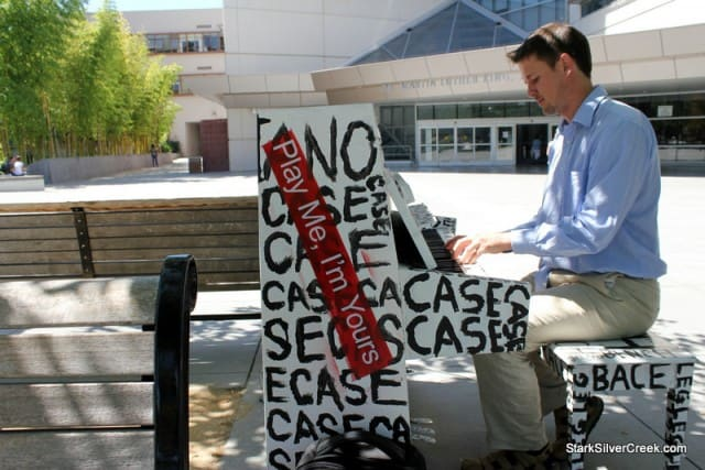 Luke Jerram plays one of his street pianos in front of San Jose's MLK library