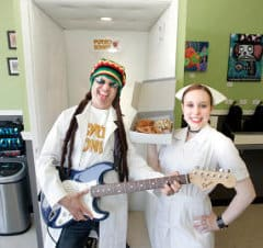 Jordan Zweigoron, chief psycho, and Dylan Syrett, nurse,  stand with guitar and donuts in front of the shop's new music studio, where customers can play the electric guitar.  (George Sakkestad/Campbell Reporter)