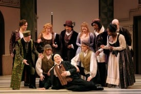 To earn his master's sympathy (and get himself out of trouble), Scapin (Bill Irwin, front and center) pretends to be dying, as the cast looks on. Photo by Kevin Berne.