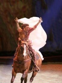 A trick rider gallops to center stage in the return  of CAVALIA under the White Big Top by AT&T Park in San Francisco.  Photo Credit: Frédéric Chéhu