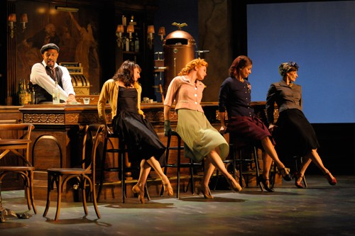 The Musician (Gregory Wallace) keeps the drinks coming while the women wait for their men to return from World War II (from left: Lorena Feijoo, Sara Hogrefe, Rachel Ticotin, Sabina Allemann). Photo by Kevin Berne.