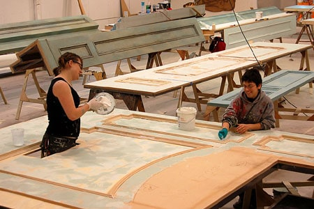 Erin Wilson and Christina Barretti-Sigal paint and distress a set wall in the scene shop at the Tony Award-winning Berkeley Repertory Theatre. Photographer: Lisa Lázár