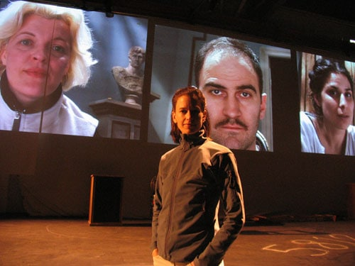 During a rehearsal, director Kim Collier stands on the No Exit set, with the cast (from left: Lucia Frangione, Andy Thompson, and Laara Sadiq) projected on screens behind her. Photo by Nathan Medd.