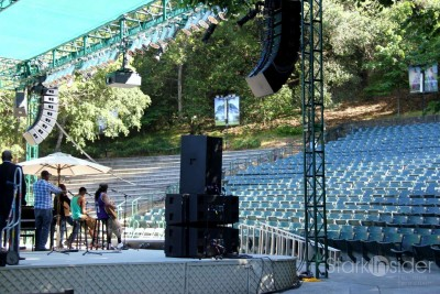 The outdoor theater is surrounded by lush landscaping, soaring trees.