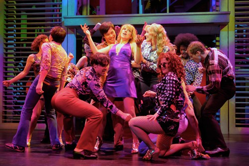 Connie Bradshaw (Julie Reiber, center, purple dress) gives newcomer Mary Ann Singleton (Betsy Wolfe, center, blue shirt) a taste of the big city in a disco. Photo by Kevin Berne.