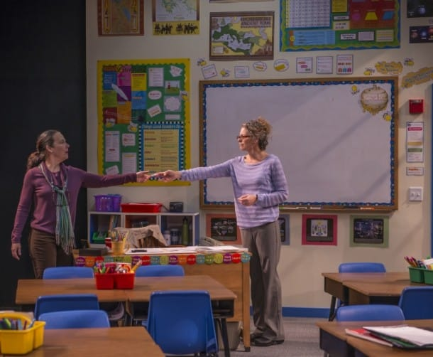 Heather (r. Stacy Ross) gives Corryn (l. Jamie Jones ) a note that was passed to Gidion during class in 'Gidion's Knot'.