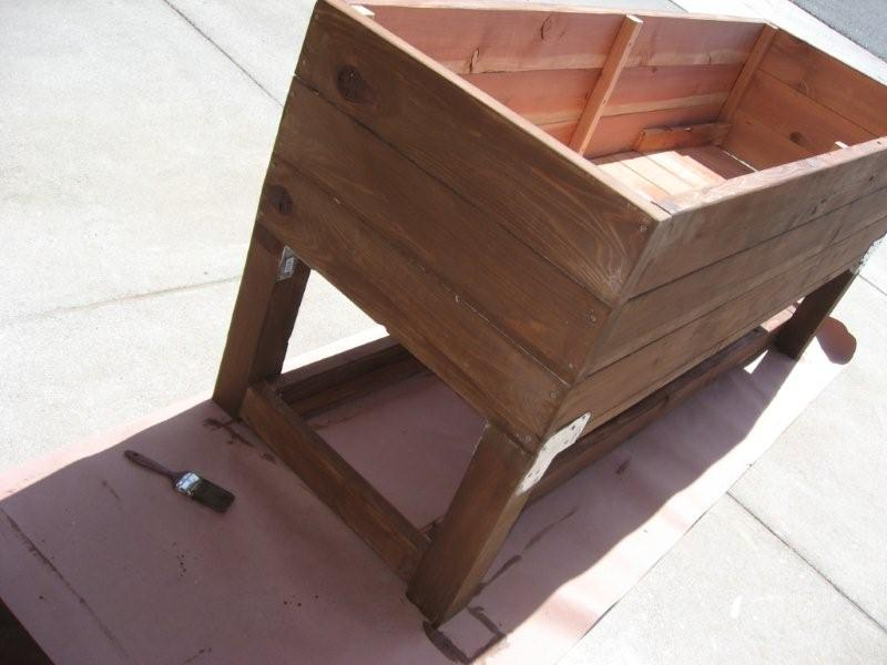 Applying a coat of stain a wooden DIY vegetable planter box - almost done!